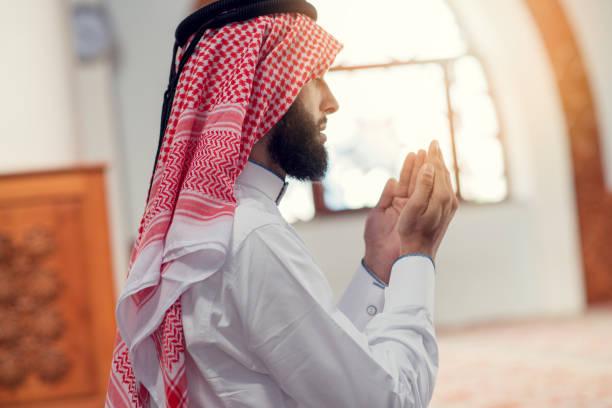 Religious muslim man praying inside the mosque.